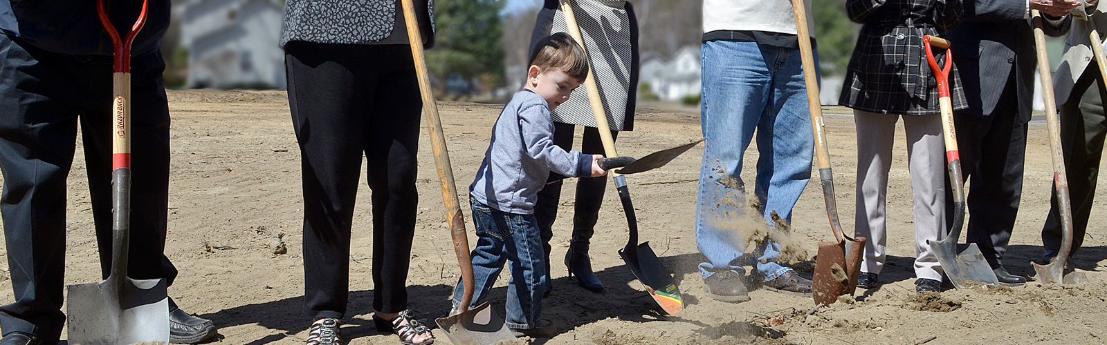 Three adults' legs and one child digging dirt with shovels at a ground breaking.