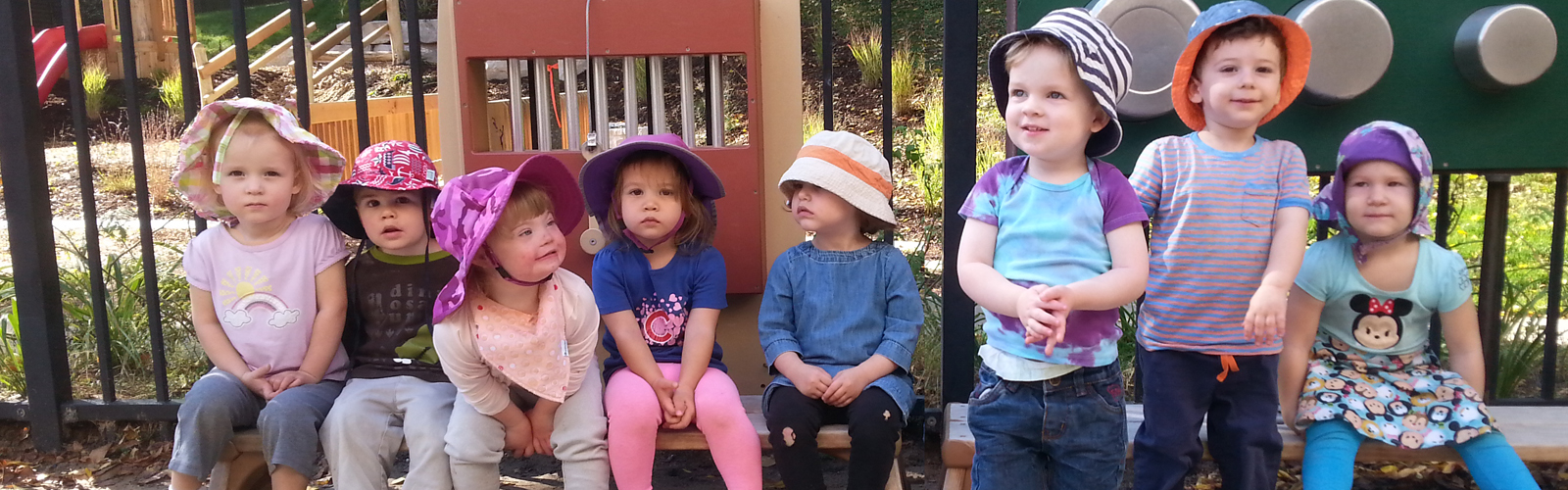 Six children wearing hats sitting on outdoor play equipment.