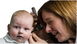 Doctor examining infant's ear