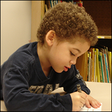 Young boy coloring on paper at a desk with a bookshelf in the background.