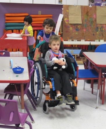 Child pushing another child in a wheelchair holding a stuffed animal