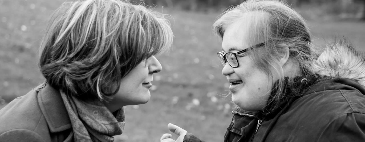Woman with short hair smiling and looking at a young woman with Down syndrome, who is smiling and looking at the woman with short hair. Grass and trees in the background.