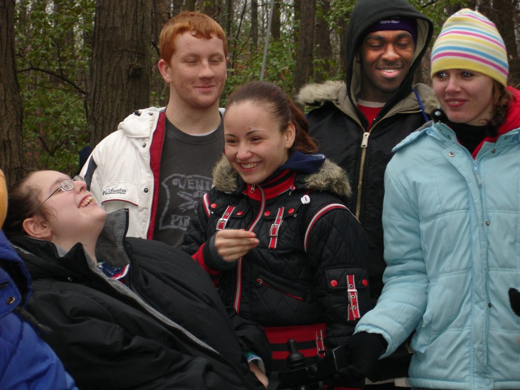 Five young adults with coats on smiling together. One young woman is laughing leaning back, looking at the other young adults. Trees in the background.