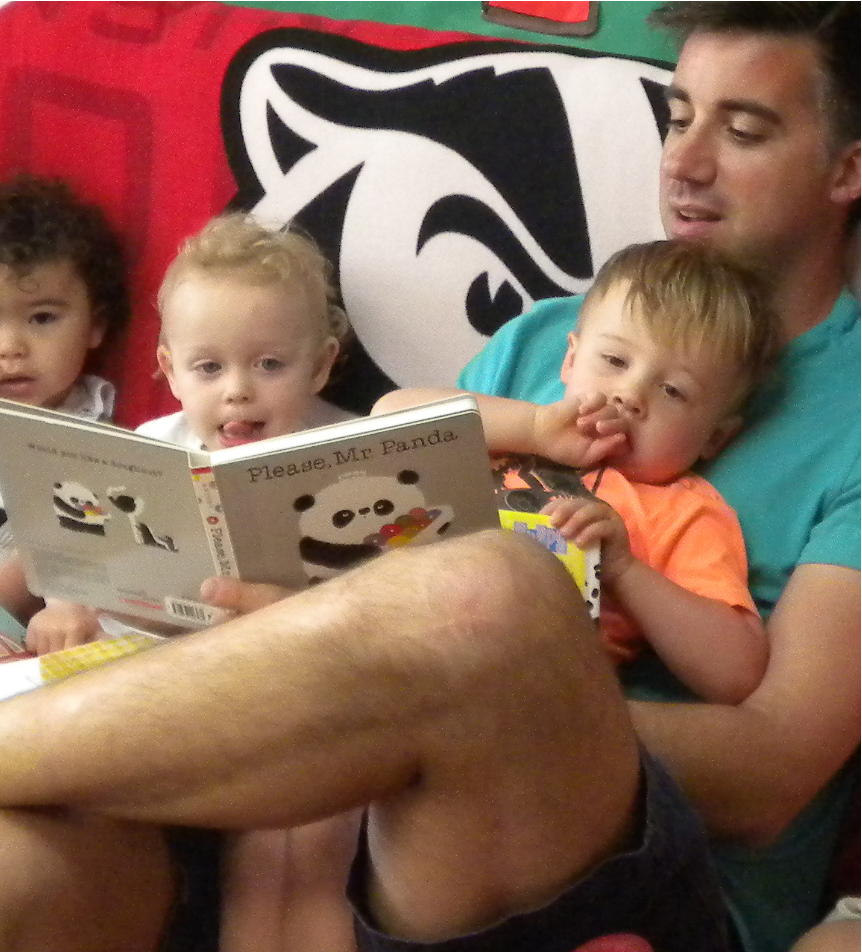 A man reads a book to three young children in his lap