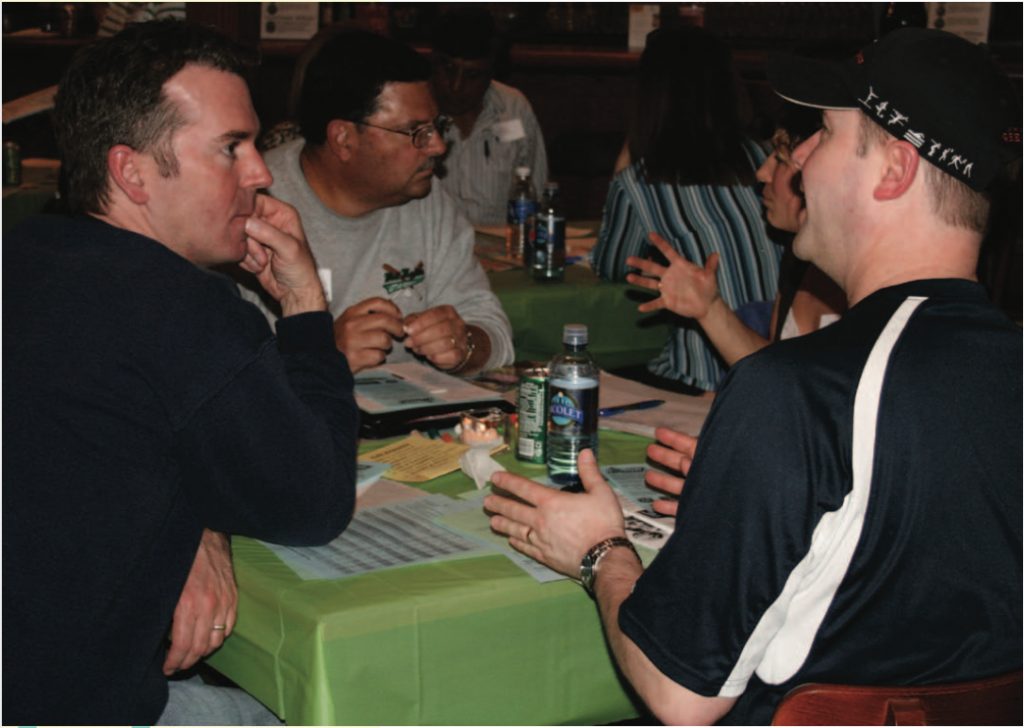 A small group sits at a table engaging in community conversation