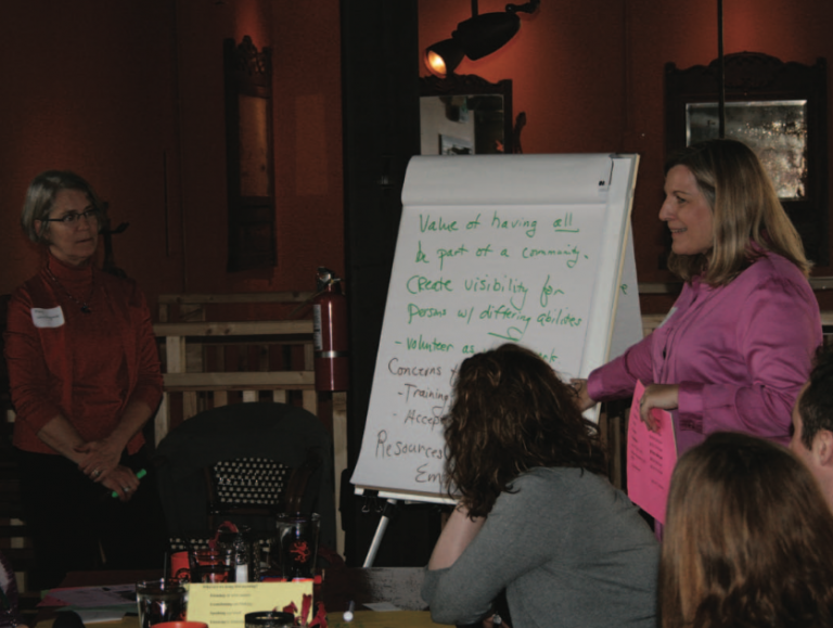 Community conversation organizers engage a group with an oversized notepad