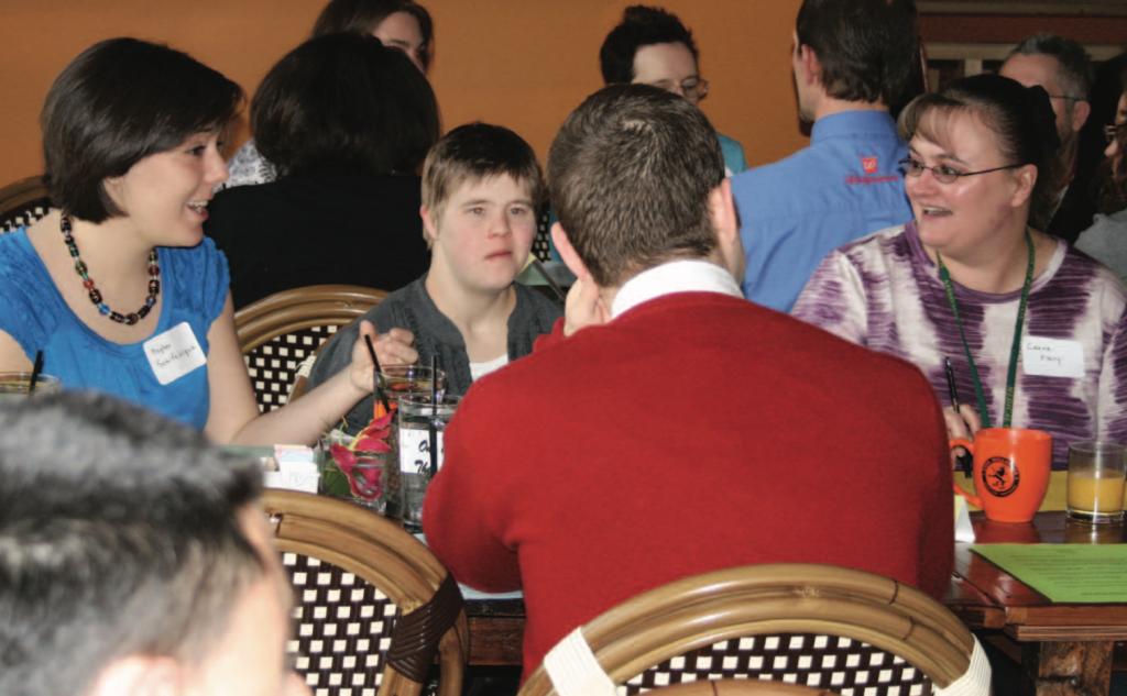 A small group at a restaurant table participate in intentional dialogue