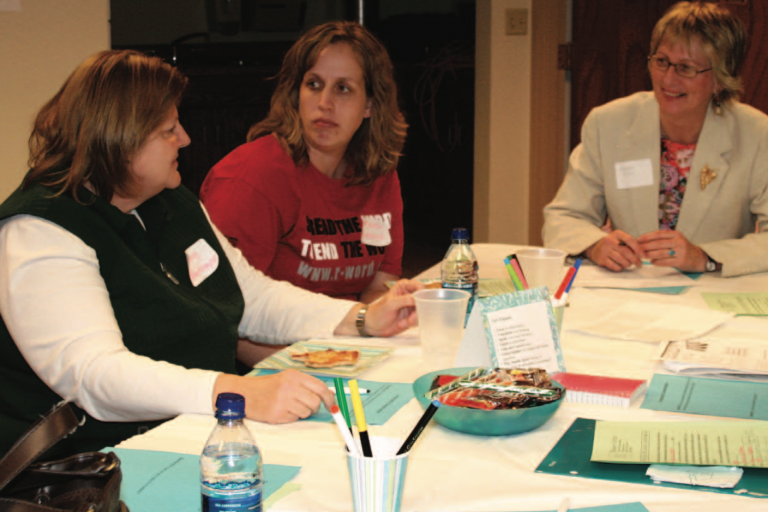 Three women engaged in community conversation at a table