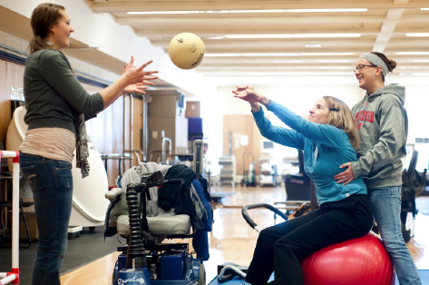 Adult woman reaching her arms out to catch a ball thrown by a woman sitting on an exercise ball supported by another woman in an indoor gym.