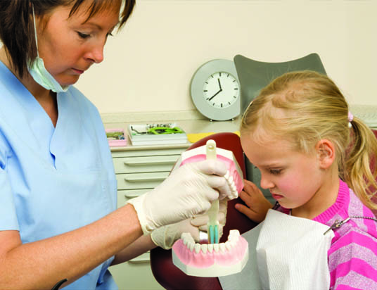 dentist with young girl looking at teeth