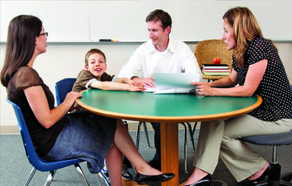 Educational professional, child, male and female caregiver sitting at a table talking to each other in a classroom Page 38