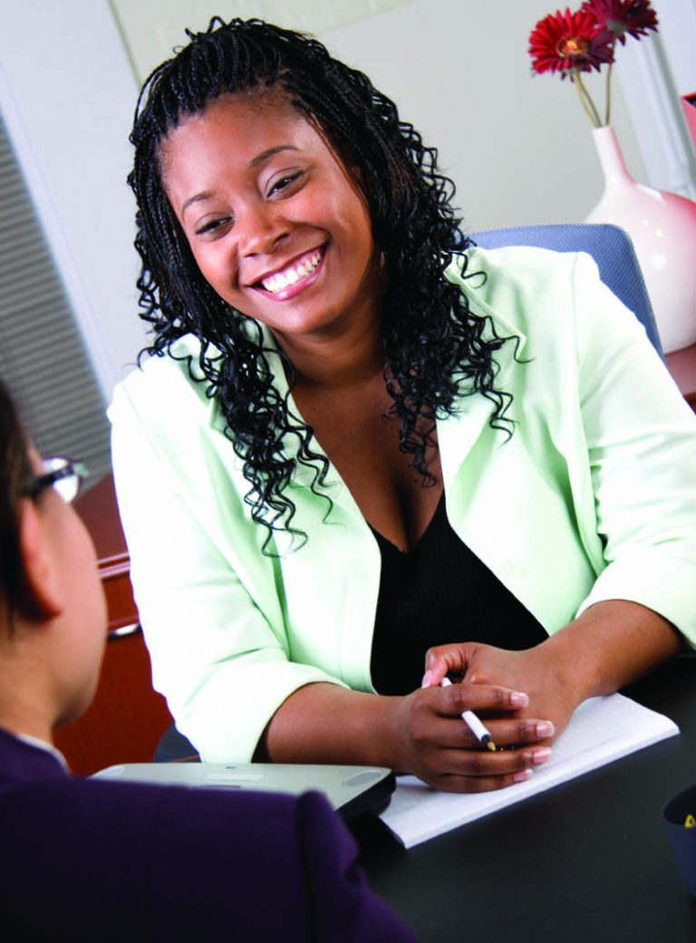 Smiling black woman looking at a individual person sitting across from her.