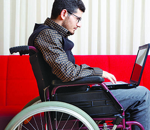 Young man in a wheelchair using a laptop.