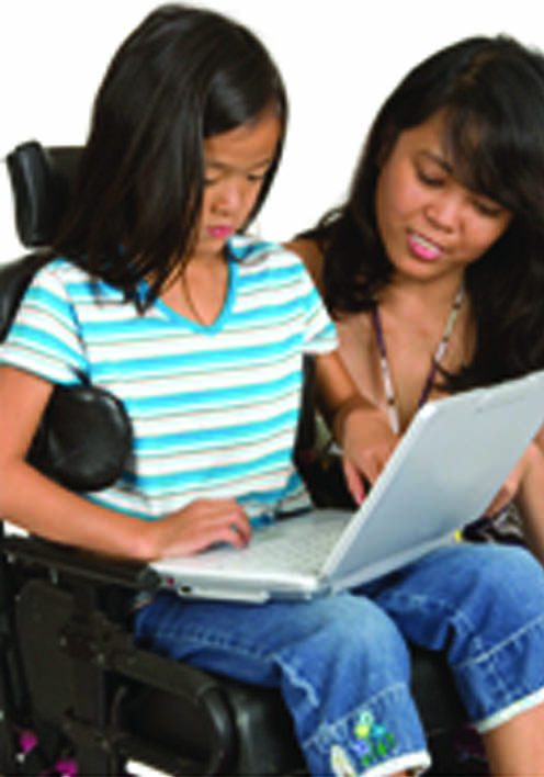 Youth in wheelchair on a laptop with a adult looking on next to her.