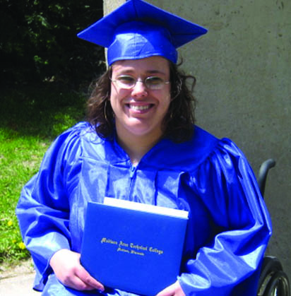 Smiling young women in a graduation cap and gown in a wheelchair holding a diploma.