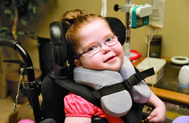 Smiling girl in a wheelchair.