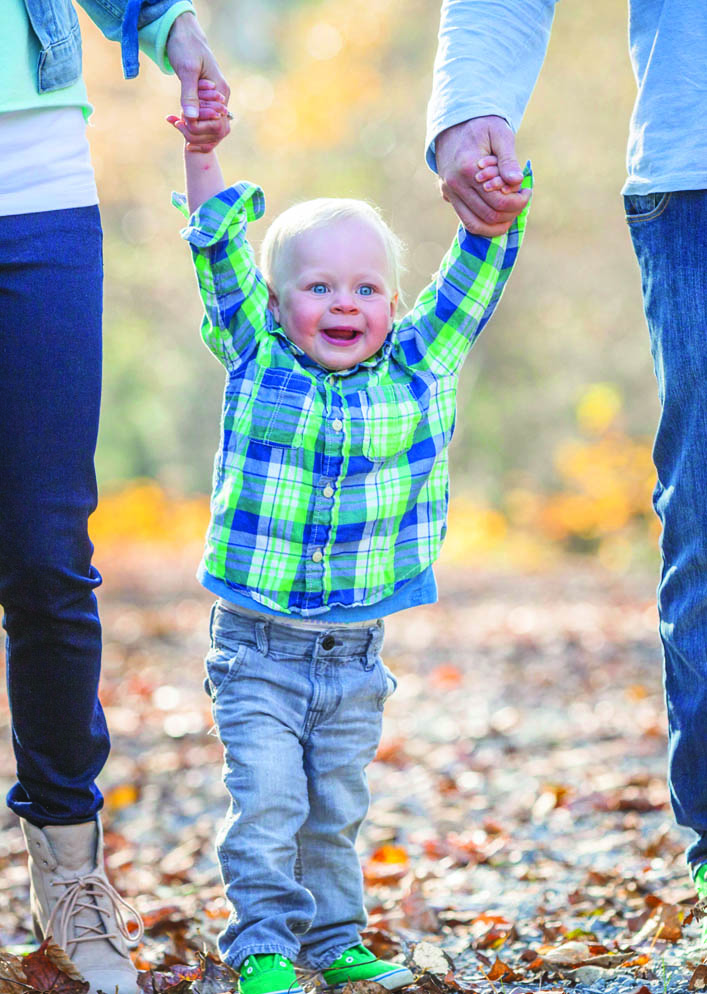 boy holding onto both parents hands as he walks