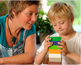 child building a stack of blocks with teacher watching