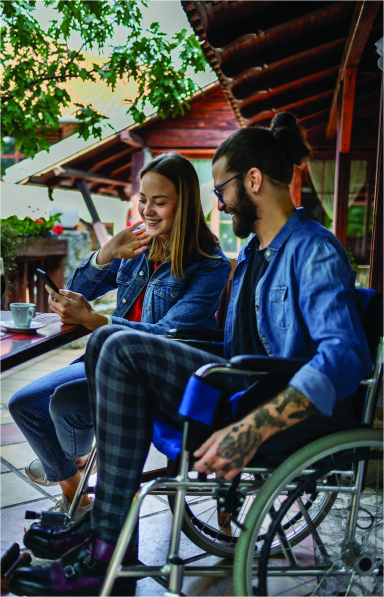 Man in wheelchair talking to woman who is showing him something on her phone