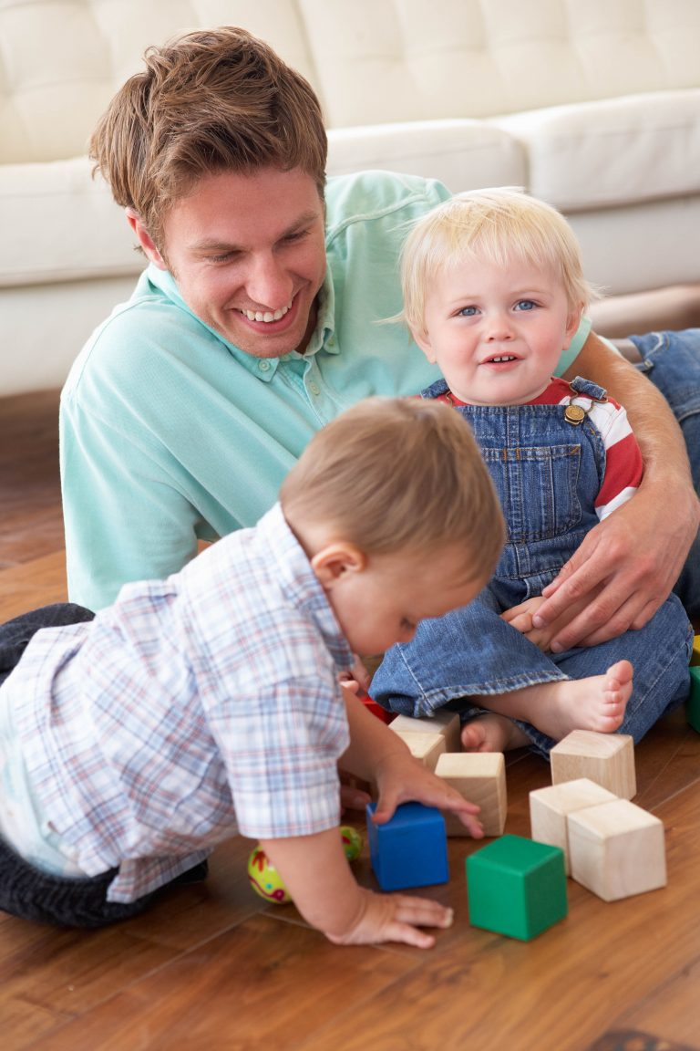 Father playing with colored blocks with his two young sons.