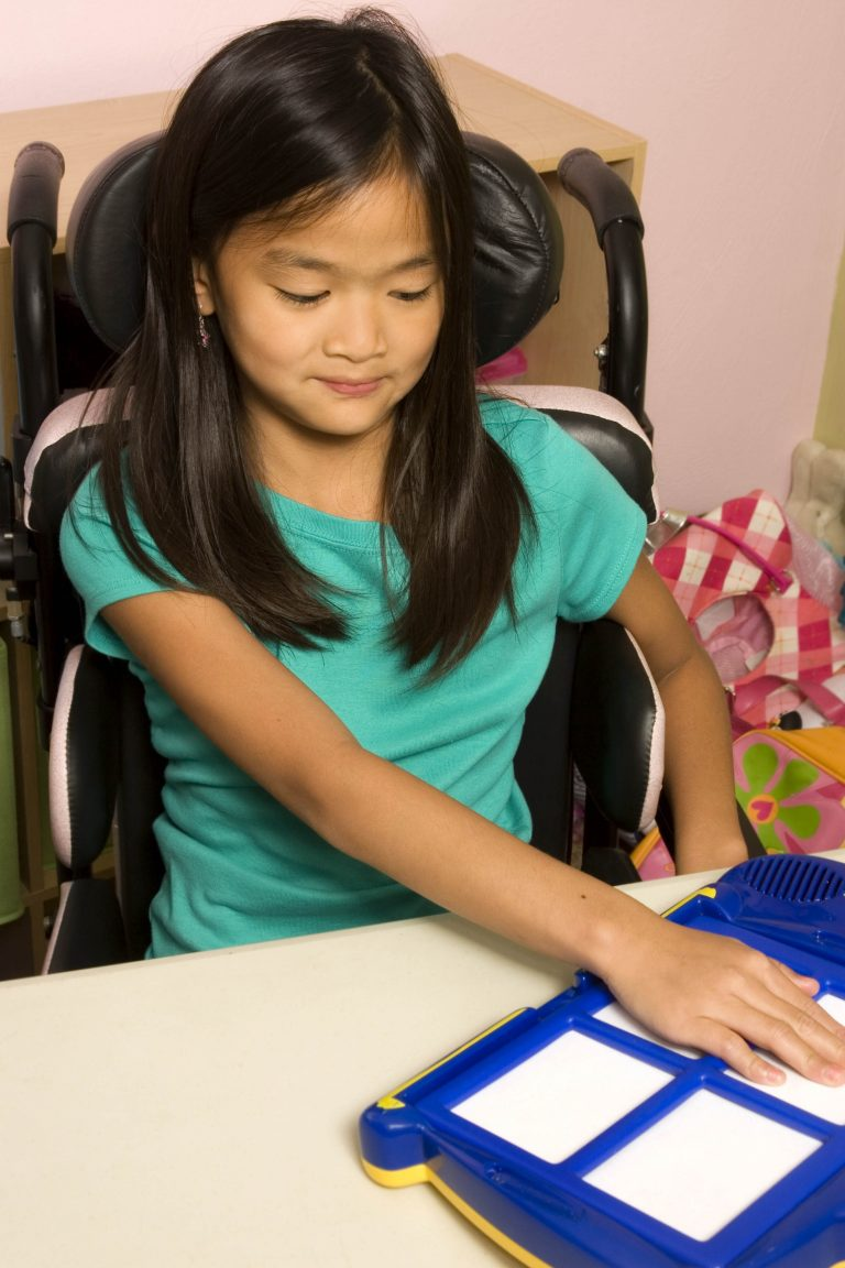 Girl in wheelchair pushes on assistive technology equipment to communicate